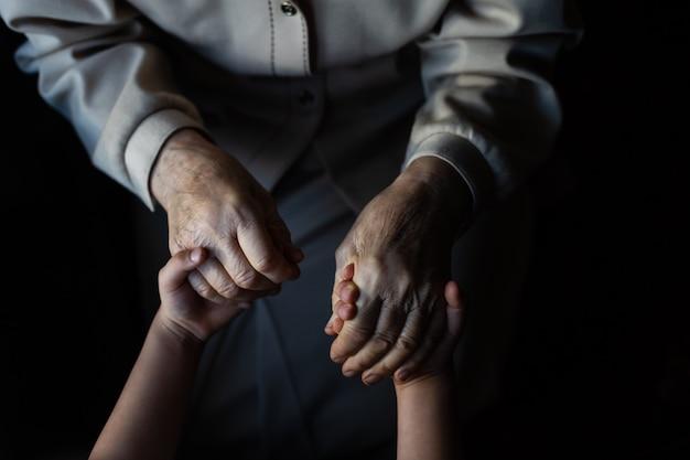 Mała dziewczynka i bardzo stara kobieta. małe dziecko przytulanie babci. wnuczka