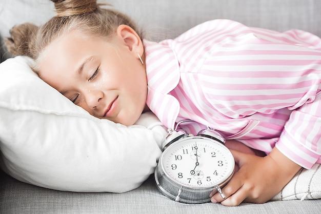 Mała dziewczynka i budzik. śmieszne dziecko z zegarem w godzinach porannych.