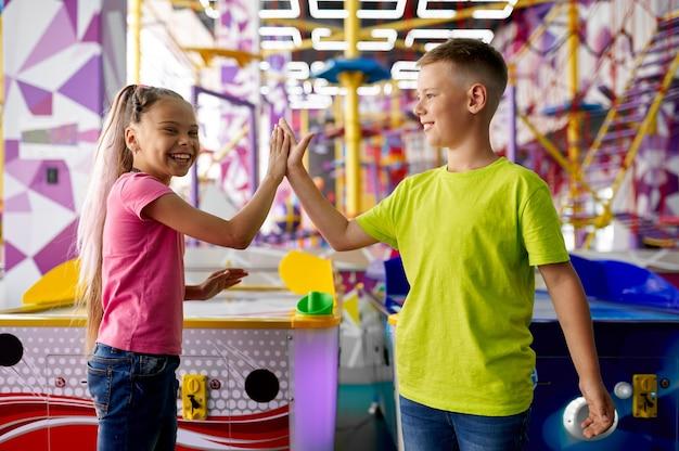 Mała dziewczynka i chłopiec grają w cymbergaja w centrum rozrywki. dzieci bawiące się, sportowa rywalizacja dzieci na placu zabaw, szczęśliwe dzieciństwo