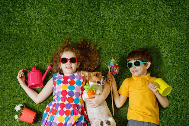 Mała dziewczynka i chłopiec i jego pies, leżąc na zielonej trawie.