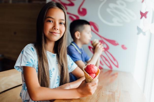 Mała dziewczynka i chłopiec jedzą lody w kawiarni