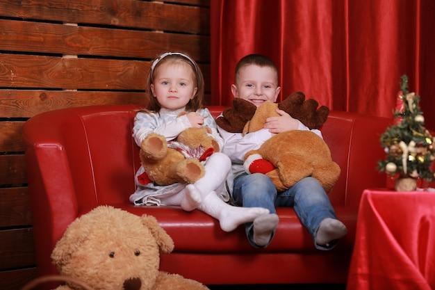 Mała dziewczynka i chłopiec na kanapie w studio boże narodzenie w czerwonych kolorach. choinka i misia na ścianie.