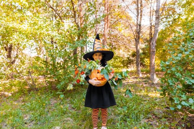 Mała dziewczynka i chłopiec rzeźbienie dyni na halloween. ubrane dzieci oszukiwanie lub leczenie. cukierek albo psikus dla dzieci. dziecko w stroju czarownicy grając w jesiennym parku. maluch dzieciak z jack-o-lantern.