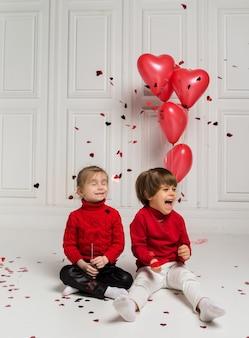 Mała dziewczynka i chłopiec siedzą i bawią się z konfetti na białym tle z czerwonymi balonami