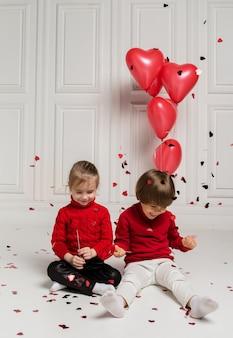 Mała dziewczynka i chłopiec siedzą i łapią konfetti na białym tle z czerwonymi balonami