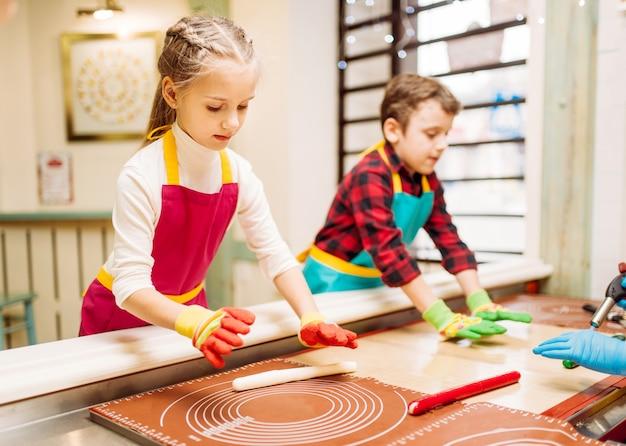 Mała dziewczynka i chłopiec uczą się robić karmel w warsztacie w cukierni. wakacyjna zabawa w sklepie ze słodyczami. proces przygotowania lollipopa