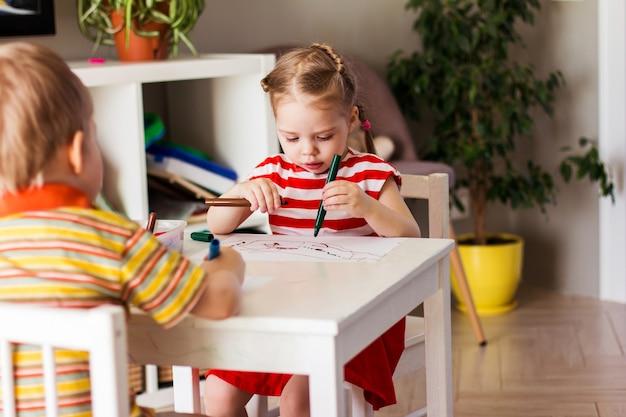 Mała dziewczynka i chłopiec w domu siedzą przy stole i rysują markerami