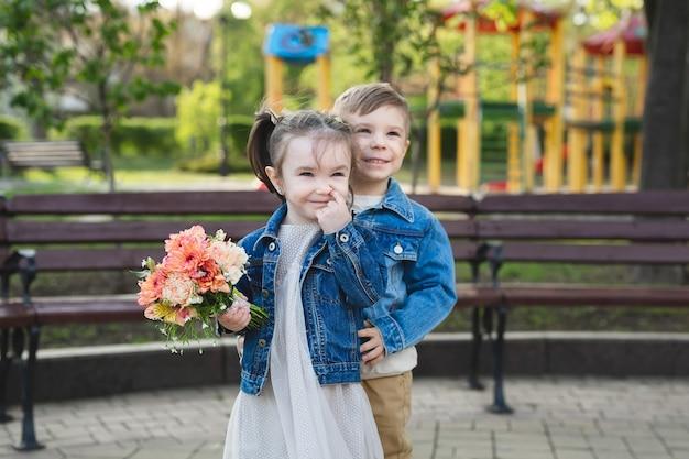 Mała dziewczynka i chłopiec w parku z bukietem kwiatów.
