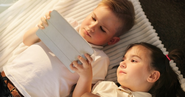 Mała dziewczynka i chłopiec za pomocą cyfrowych tabletów