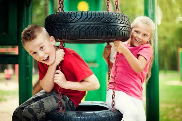 Mała dziewczynka i chłopiec, zabawy na placu zabaw