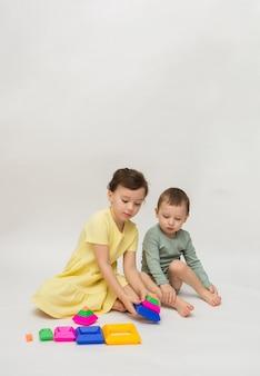 Mała dziewczynka i chłopiec zbierają wielokolorową piramidę na białym tle