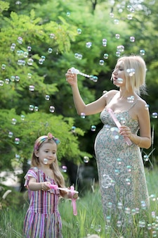 Mała dziewczynka i jej ciężarna matka, grając w dmuchanie baniek mydlanych, koncepcja szczęśliwego dzieciństwa, plenerowe zdjęcie