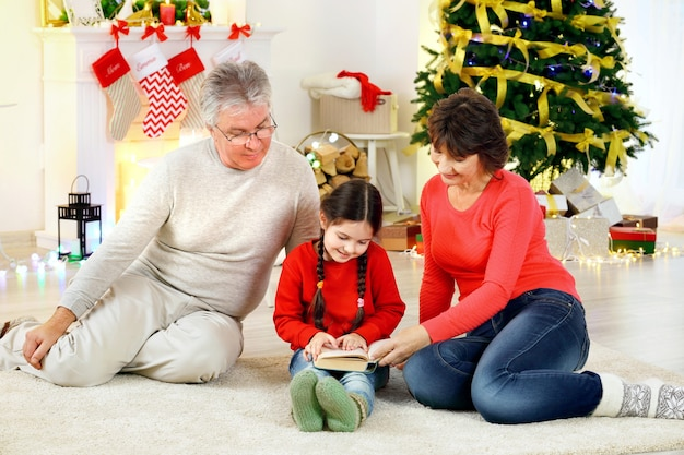 Mała dziewczynka i jej dziadkowie czytają książkę w salonie urządzonym na boże narodzenie