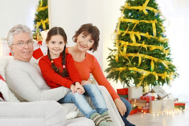 Mała dziewczynka i jej dziadkowie siedzą na kanapie w salonie udekorowanym na boże narodzenie