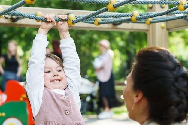 Mała dziewczynka i jej mama bawią się na placu zabaw w miejskim parku