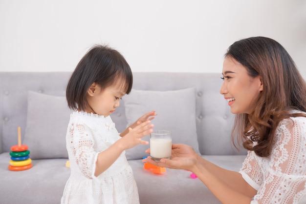 Mała dziewczynka i jej mama pije mleko, siedząc na kanapie w domu. macierzyństwo i opieka, zdrowe odżywianie i styl życia, koncepcja wczesnego rozwoju, miejsce kopiowania