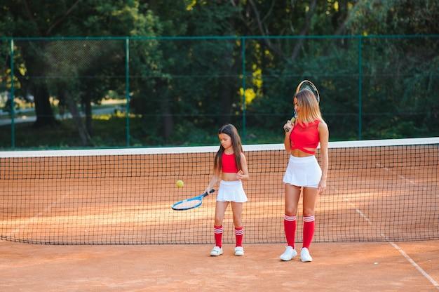 Mała dziewczynka i jej matka, grając w tenisa na korcie