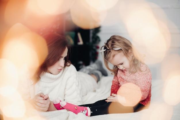 Mała dziewczynka i jej matka na łóżku z bokeh skutkiem