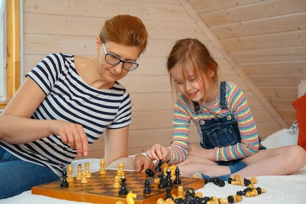 Mała dziewczynka i jej matka rysuje figury na szachownicy. gra w szachy