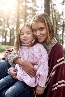 Mała dziewczynka i jej matka w lesie. dziewczyna i jej matka patrzą w kamerę. kobieta ma na sobie stylową czapkę i płaszcz z dzianiny, dziewczyna w różowym jasnym swetrze