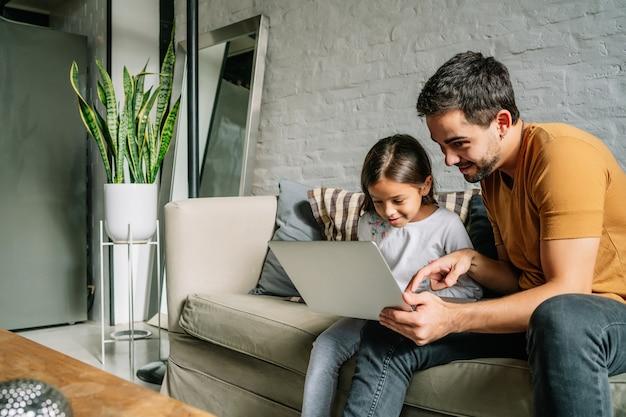 Mała dziewczynka i jej ojciec bawią się razem i używają laptopa, siedząc na kanapie w domu. koncepcja rodziny jednorodzicielskiej.
