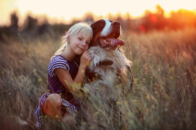 Mała dziewczynka i jej pies spacerują po łące w wysokiej trawie o zachodzie słońca.