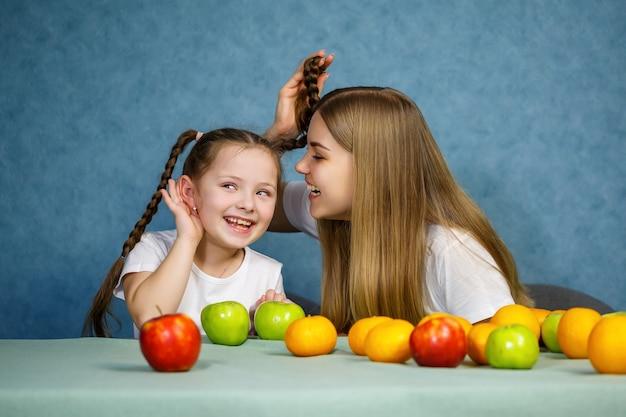 Mała dziewczynka i mama bawią się owocami i wygłupiają. noszą t-shirty