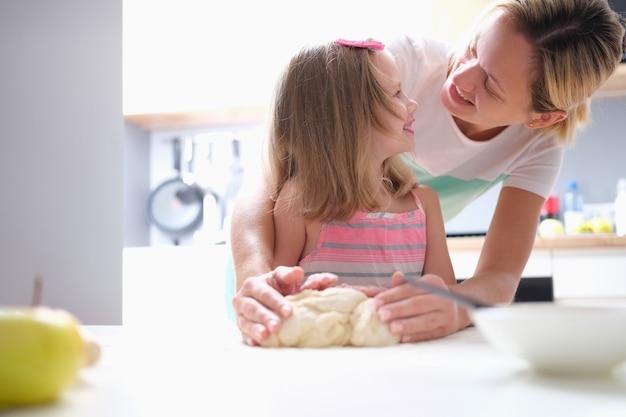 Mała dziewczynka i mama robi ciasto w domu. koncepcja opieki nad dzieckiem