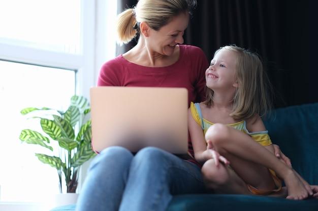 Mała dziewczynka i mama siedzą na kanapie z laptopem na kolanach i rozmawiają