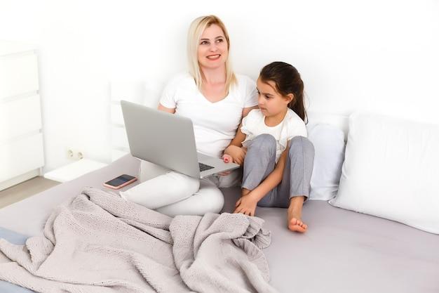 Mała dziewczynka i mama z laptopem na łóżku