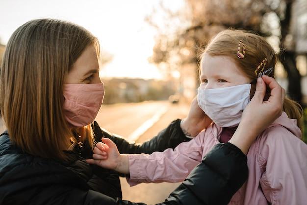 Mała dziewczynka i matka nosi maski na ulicy