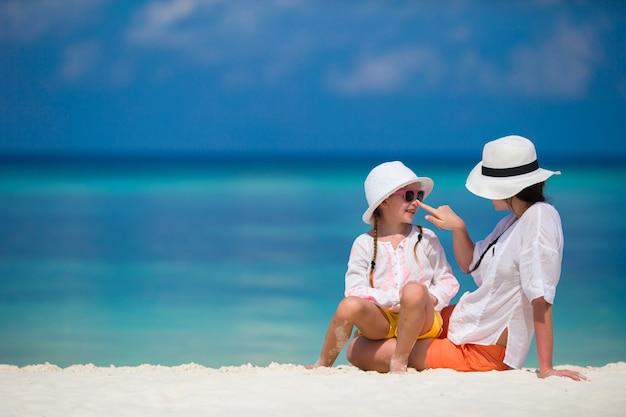 Mała dziewczynka i młoda matka podczas wakacji na plaży