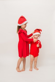 Mała dziewczynka i pełnometrażowy chłopiec w czerwonych czapkach z lizakami na białej ścianie z kopią miejsca