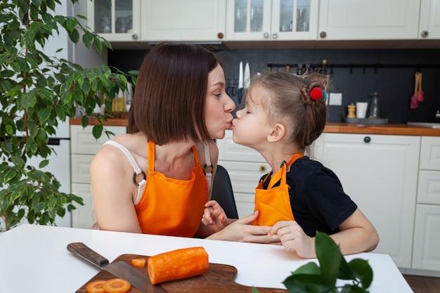 Mała dziewczynka i piękna mama gotują warzywa w domowej kuchni