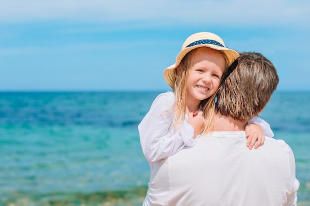 Mała dziewczynka i szczęśliwy tata ma zabawę podczas wakacje na plaży