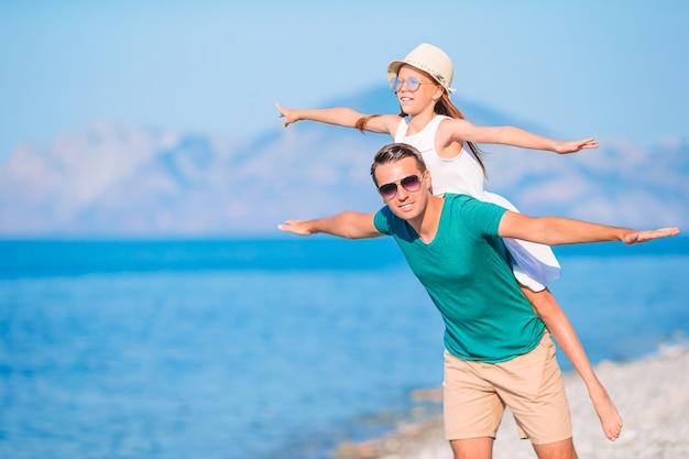 Mała dziewczynka i szczęśliwy tata, zabawy podczas wakacji na plaży
