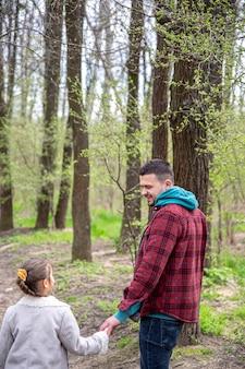 Mała dziewczynka i tata spacerują w parku wczesną wiosną w chłodne dni.
