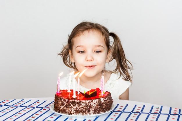 Mała dziewczynka i tort urodzinowy, zdmuchuje świeczki, robi życzenie, ciasto i świece, prezenty urodzinowe, rodzina, mama i tata
