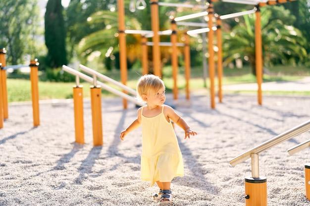 Mała dziewczynka idzie wzdłuż placu zabaw obok poziomych prętów