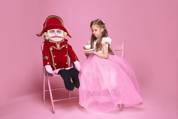 Mała dziewczynka jako baletnica piękna w różowej długiej sukni z dziadkiem do orzechów w różowym studio z filiżanką herbaty