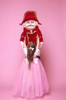 Mała dziewczynka jako baletnica piękna w różowej długiej sukni z dziadkiem do orzechów w różowym studio
