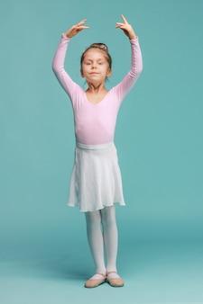Mała dziewczynka jako tancerka baleriny na niebieskim studio