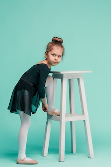 Mała dziewczynka jako tancerka baleriny w pobliżu krzesła na niebieskim studio