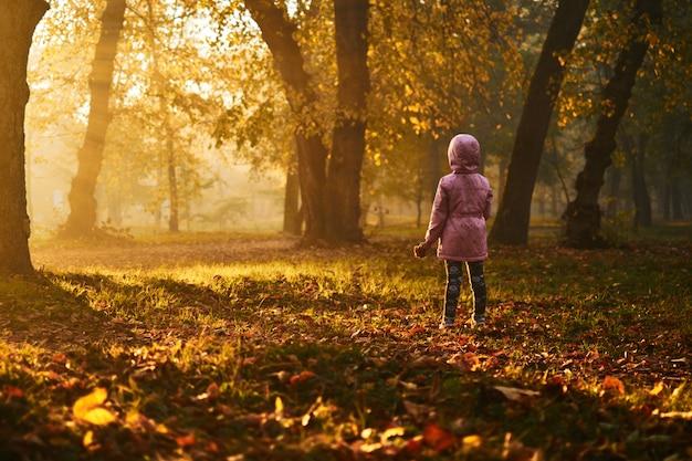 Mała dziewczynka je bułkę w piękny jesienny mglisty dzień o wschodzie słońca w różowej kurtce. przekąska w naturze