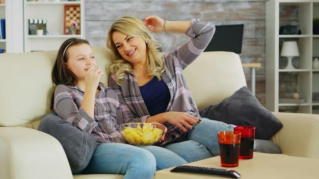 Mała dziewczynka je frytki podczas oglądania filmu w telewizji z matką. matka i córka relaks.