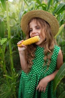 Mała dziewczynka je kukurydzę na polu