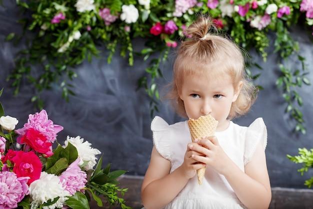 Mała dziewczynka je lody. dekoracja kwiatowa we wnętrzu. portret pięknej dziewczyny