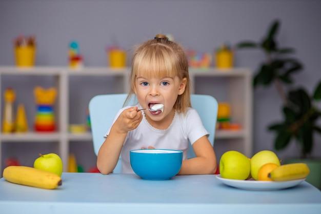 Mała dziewczynka je owsiankę lub twarożek na śniadanie