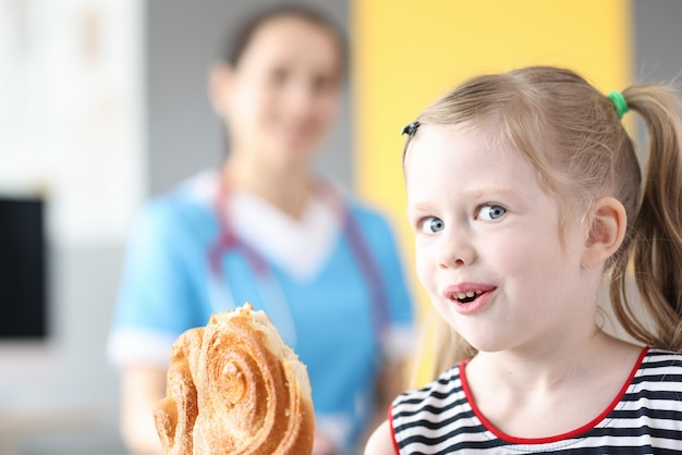 Mała dziewczynka je słodkie słodycze na tle lekarza