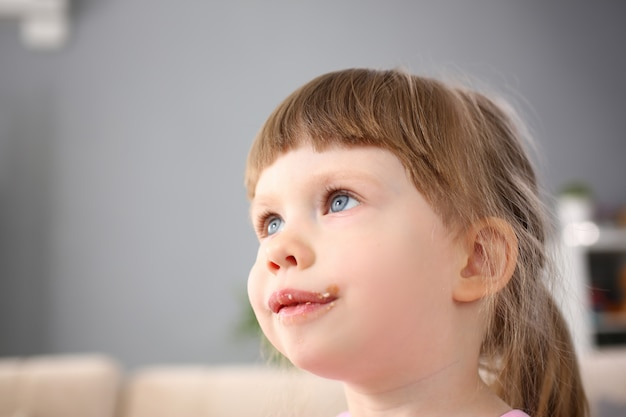 Mała dziewczynka je słodkiego czekoladowego cukierek z śladem przy jej usta